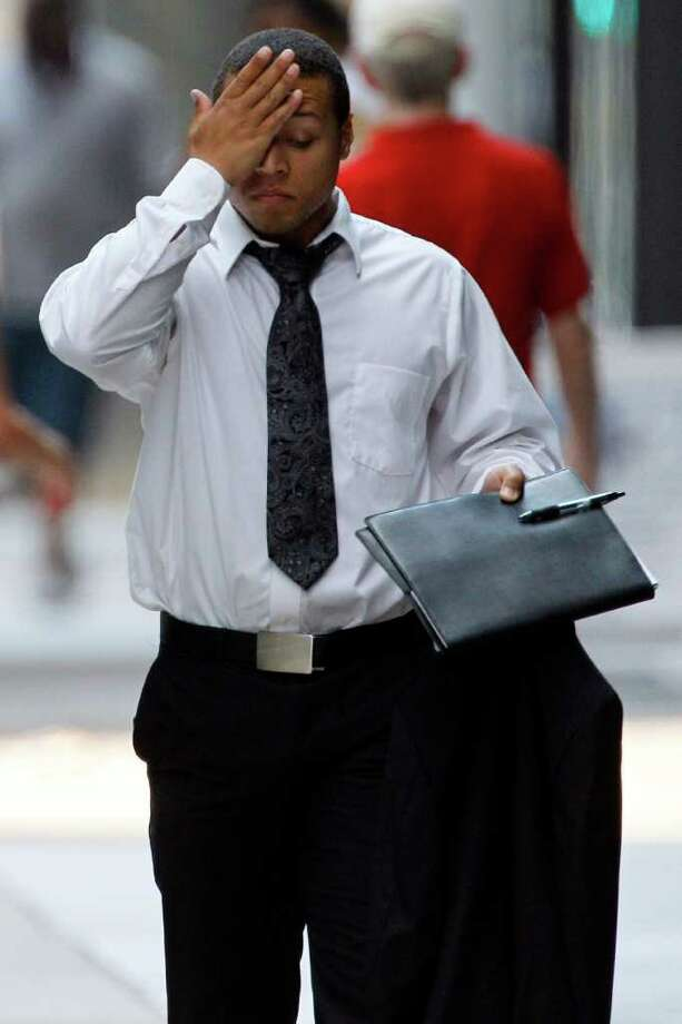 Carrying his jacket in his hand, a man with a suit wipes his brow as he walks along Market Street in the afternoon heat Friday, July 22, 2011, in Philadelphia. (AP Photo/Matt Rourke) Photo: Matt Rourke