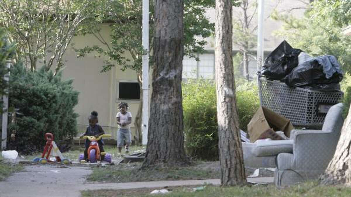 Children play amid discarded furniture and trash at the Candlewood Glen complex in northwest Houston last month.