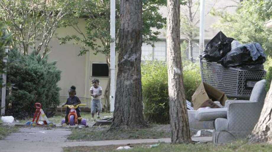 Children play amid discarded furniture and trash at the Candlewood Glen complex in northwest Houston last month. Photo: JULIO CORTEZ, CHRONICLE