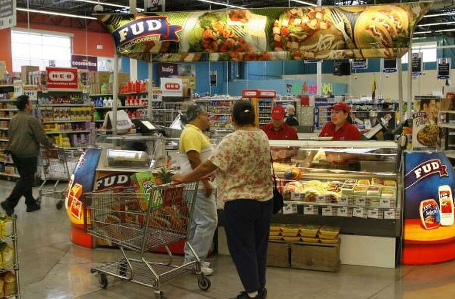 Fud's Aracely Garcia and Sofia Vega talk to customers at the deli counter in an H-E-B store at Texas 6 and Bellaire. Sigma, a Mexican food supplier, is making inroads in Houston with products many Mexican immigrants remember from back home. Photo: CARLOS ANTONIO RIOS, CHRONICLE