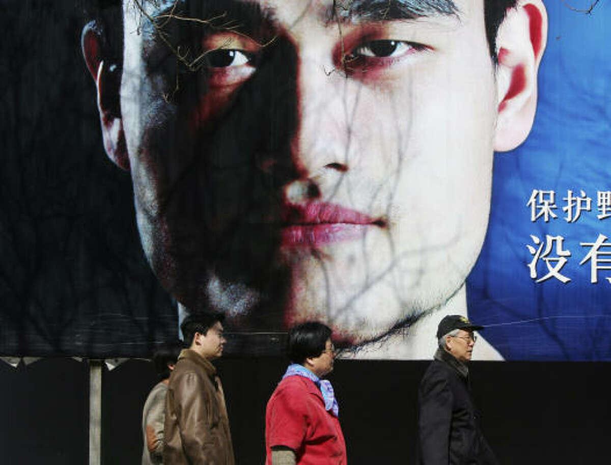 Pedestrians walk past a billboard featuring Yao Ming's face in Beijing.