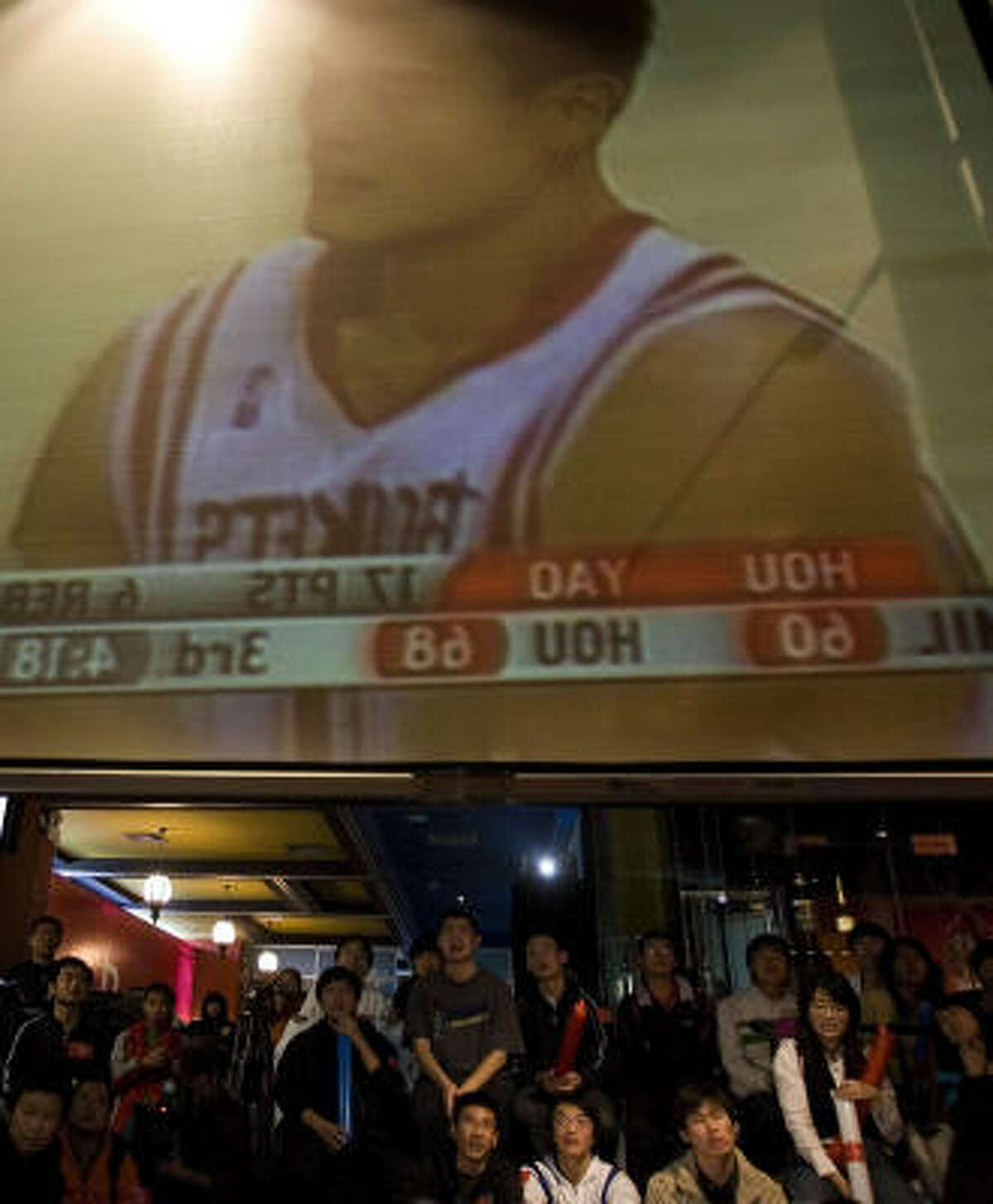 Chinese basketball fans watch the Yao Ming and the Rockets play the Milwaukee Bucks at a restaurant in Beijing.