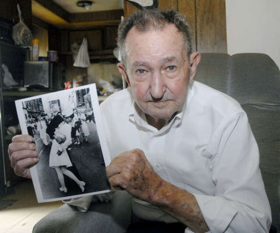 "Glenn McDuffie, 80, holds up a photo of himself kissing a nurse in Times Square to celebrate the end of World War II. The 1945 photo in Life Magazine was called ""The Kiss.'' Photo: Tim Johnson, For The Chronicle"