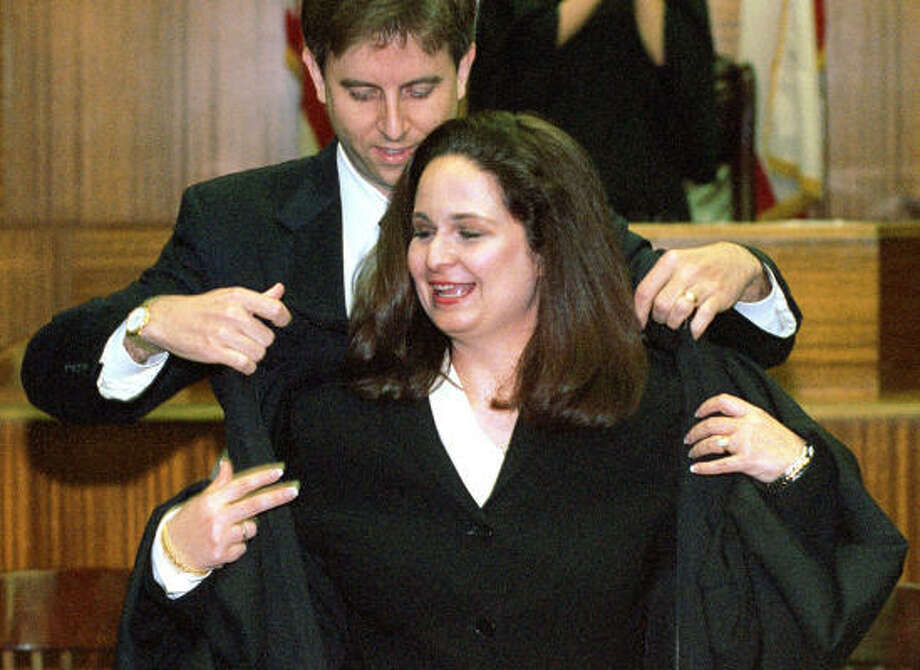 Jennifer Walker Elrod is helped with enrobing by her husband, Hal C. Elrod, after she was sworn in as judge of the 331st District Court on April 23, 2002, in Houston. Photo: Chronicle File