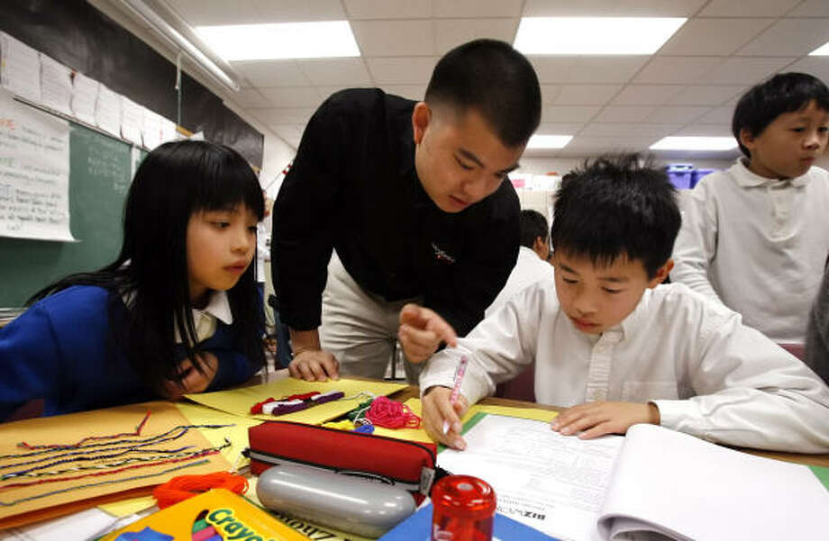 Mark Trang of Salesforce.com, center, teaches business basics to fifth-graders Tiffany Lee and David Zhong, at Jean Parker Elementary School in San Francisco. Photo: Jakub Mosur, AP