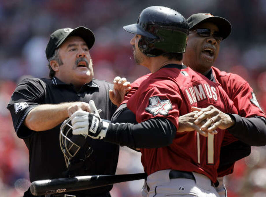 Houston's Brad Ausmus, center, is held back by manager Cecil Cooper, right, and umpire Tim Tschida, left, while yelling at Cardinals pitcher Adam Wainwright. Photo: Jeff Roberson, AP