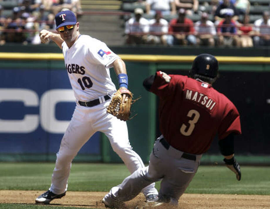 Astros second baseman Kazuo Matsui tries to break up a double play unsuccessfully as Rangers shortstop Michael Young throws to first to get the second out. Photo: LM Otero, AP