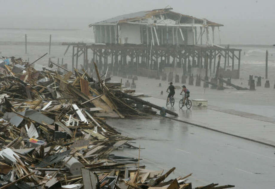 Cyclists ride past debris piled up on the seawall road after Hurricane Ike hit the Texas coast. Photo: Matt Slocum, Associated Press