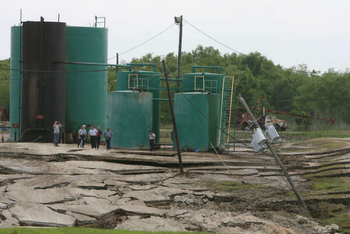 Emergency crews stand near a large sinkhole Wednesday behind the Deloach Vacuum Disposal Co., near FM 770 and FM 834. City officials estimate the size of the hole at about 200 yards wide and as much as 100 feet deep in places.