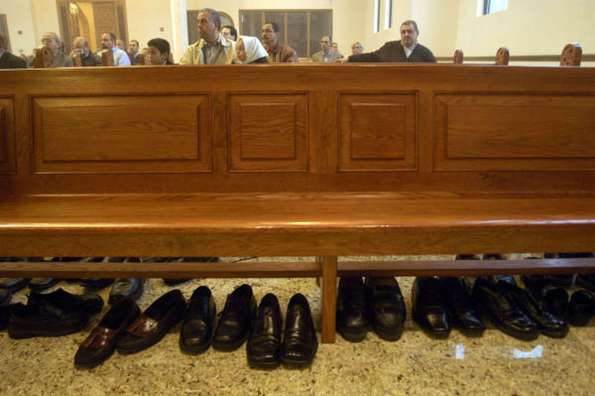 """Men removed their shoes for communion during a service at St. Mary and Archangel Michael Coptic Orthodox Church in west Houston, in accordance with Exodus 3:5 when God was talking to Moses. The verse reads, """"Take off your sandals, for the place where you are standing is holy ground."""""""