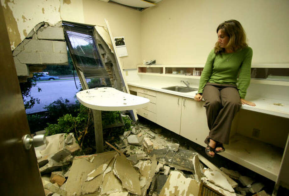 Westbury Animal Hospital employee Sharon Shorey describes the impact as she sits in an examination room destroyed when a car rammed into the clinic last week. Shorey, who was only feet away in an adjacent room when the vehicle hit, was on the job for only four days and in Houston for less than a week. Photo: Jason Brown, For The Chronicle