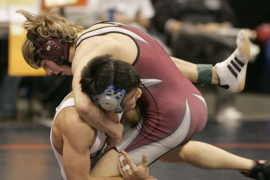 Cy-Fair's Austin McCain battled to a victory over Klein's Chris Nguyen in the 125-pound championship at the Region III Wrestling Tournament on Saturday at the Merrell Center in Katy. Photo: MARGARET BOWLES, FOR THE CHRONICLE