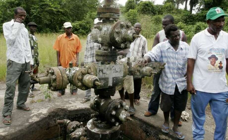 Men from Otabagi village aren't giving up cobweb-covered Oloibori Well No. 1. The unproductive tangle of pipes deep in the Nigerian bush is at the center of an increasingly vitriolic competition between two villages seeking sole ownership of the well. Photo: SUNDAY ALAMBA, ASSOCIATED PRESS