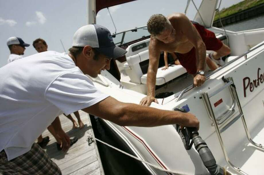 """Tyler McCreary, 17, helps boat owner Dennis Richards refuel at South Shore Harbour in League City on Saturday. Richards says high fuel prices won't keep him from taking his boat out for a spin. """"If it goes double, I don't care,"""" he said. """"It's worth it. I'd still be out here every day."""" Photo: SHARÓN STEINMANN, CHRONICLE"""