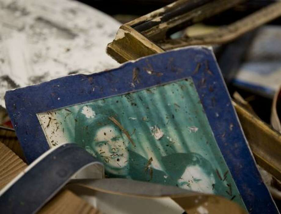 A World War II-era photo sits in a pile of items damaged by flooding. Photo: BRETT COOMER, CHRONICLE