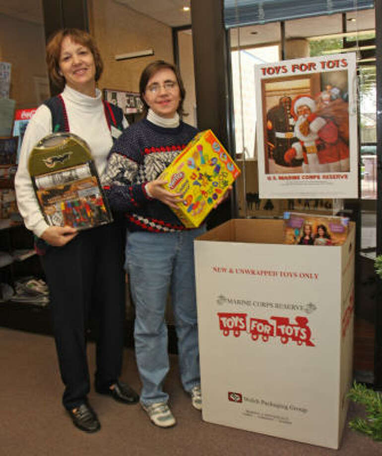 Maud Marks Library, 1815 Westgreen Blvd. in Katy, has a Toys for Tots collection box. From left are Sylvia Powers, branch librarian, and Naomi Haught, reference librarian. Photo: Suzanne Rehak, For The Chronicle