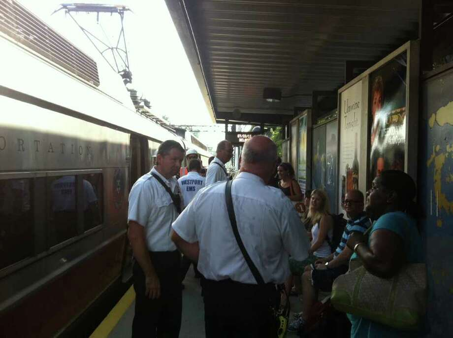 Westport Fire Chief Andrew Kingsbury, left, talks with Metro-North Railroad passengers at the Greens Farms Railroad Station on Friday afternoon after they got off a sweltering train that stalled on the tracks for about an hour. Several passengers reported being nearly overcome by scorching heat in the 100-degree range. Photo: Paul Schott / Westport News