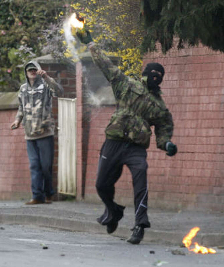 A masked youth throws a petrol bomb at PSNI officers close to were a leading Irish Republican was arrested, Saturday, in connection with the recent murders of two British soldiers, over a hundred Irish Republicans blocked the main railway line and began rioting in Lurgan, Northern Ireland, Saturday. Photo: PETER MORRISON, AP