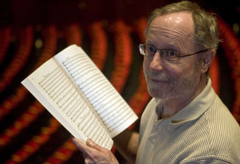 Houston Symphony librarian Tom Takaro holds a new book of music. Photo: James Nielsen, Chronicle