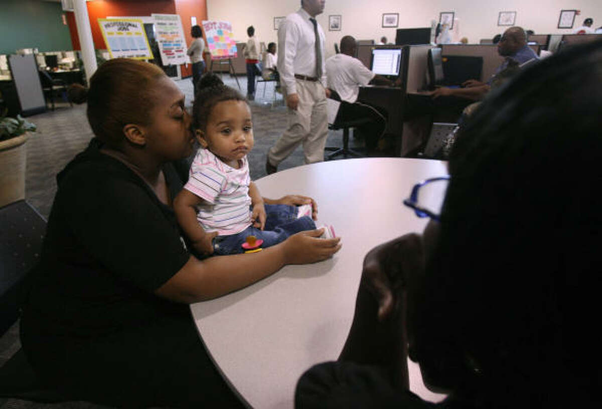 Travoya Scott, 19, holds her 8-month-old daughter, Mala Rogers, while waiting to see a job counselor with her mother, Sherry Scott, 49, at Workforce Solutions in Houston on Wednesday. Both women said they have had trouble finding permanent jobs.