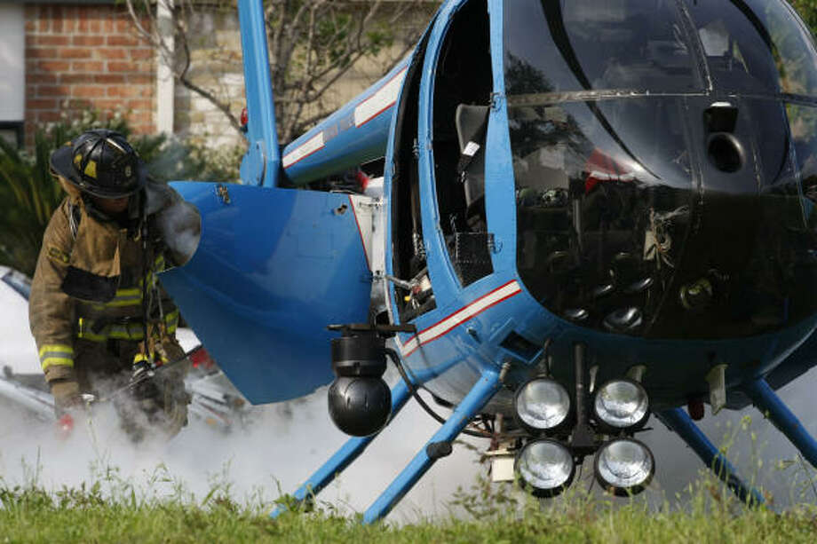 A Houston firefighter responds to the emergency landing of a Houston Police Department chopper near the Dennis-Brazos intersection. Photo: Julio Cortez, Chronicle