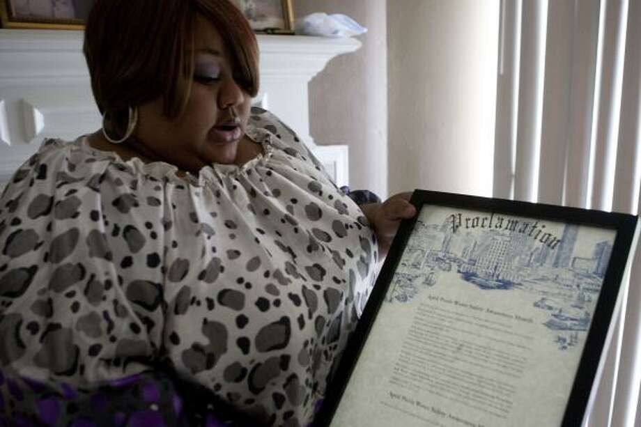 Deonesia Grays, holding a city proclamation for pool safety awareness, founded a group after her child drowned. Photo: James Nielsen, Chronicle