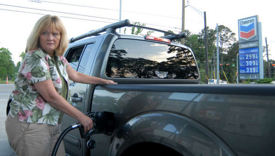 Joy Davies warily looks at the gas pump as she fills her truck up with gasoline on FM 1488 near FM 2978. Photo: Brad Perkins, For The Chronicle