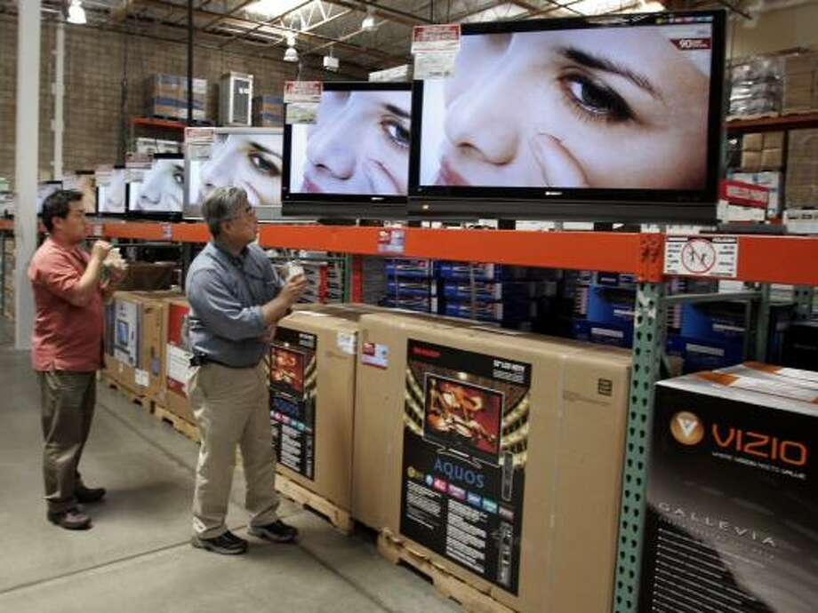 Customers scrutinize TV screens at a Costco store in Mountain View, Calif., on Thursday. Retailers in general were disappointed by consumer spending in April, although Costco's same-store sales increased by 7 percent. Photo: PAUL SAKUMA, ASSOCIATED PRESS