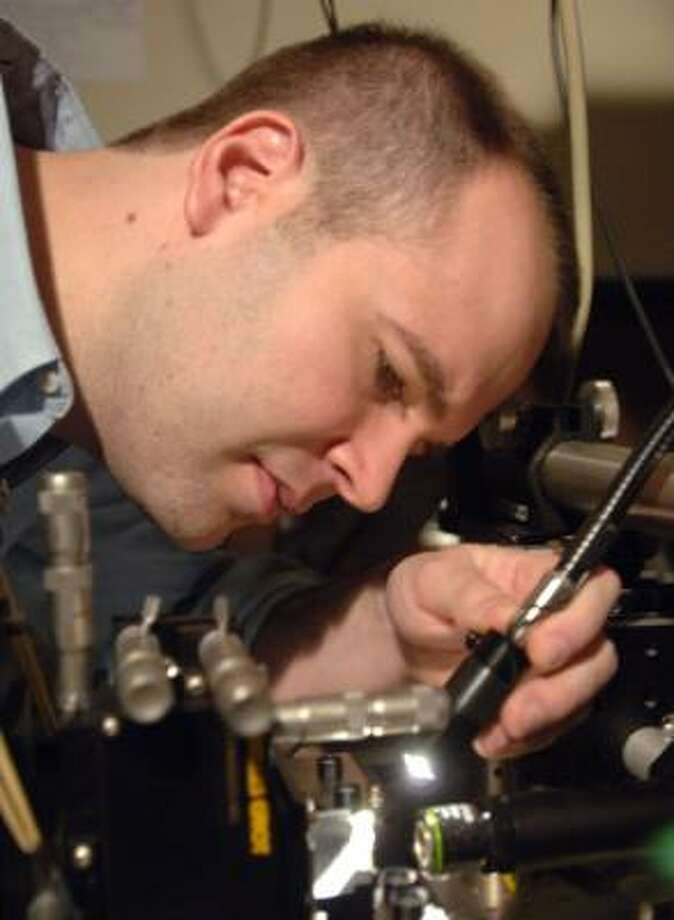 Peter Rakich, a graduate student at MIT, works on developing optics that can fit on a microchip. Photo: Donna Coveney, MIT