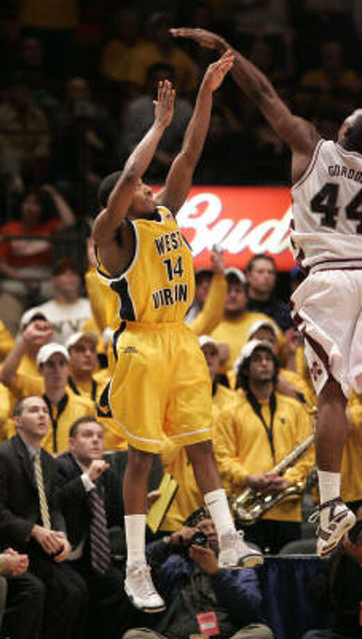 West Virginia's Darris Nichols launches the game-winning 3-pointer past Mississippi State's Jamont Gordon. Photo: Seth Wenig, Associated Press