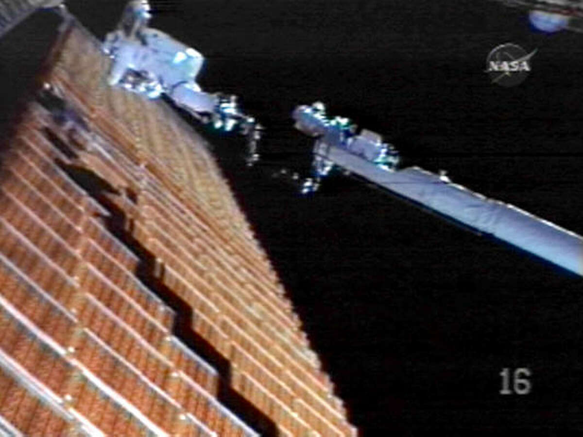 In this image from NASA, astronaut Scott Parazynski repairs the damaged solar panels on the international space station.