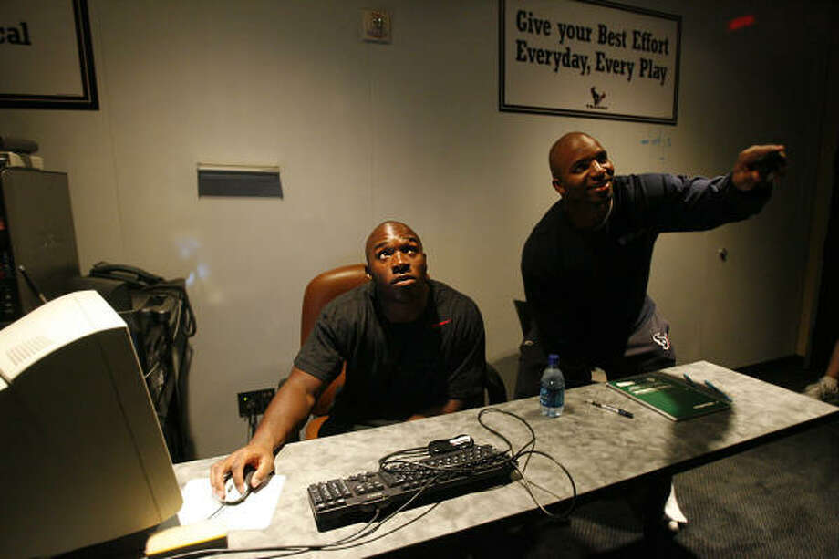 DeMeco Ryans and Morlon Greenwood watch video of team practices. The linebackers were the most productive players on defense last season. Photo: Mayra Beltran, Chronicle