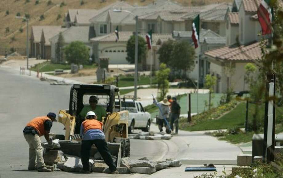 Workers finish sidewalks and curbs in a section of the Toll Brothers Country Club Estates luxury housing development in Moorpark, Calif. The builder's profit plunged 85 percent in its third quarter. Photo: REED SAXON, ASSOCIATED PRESS