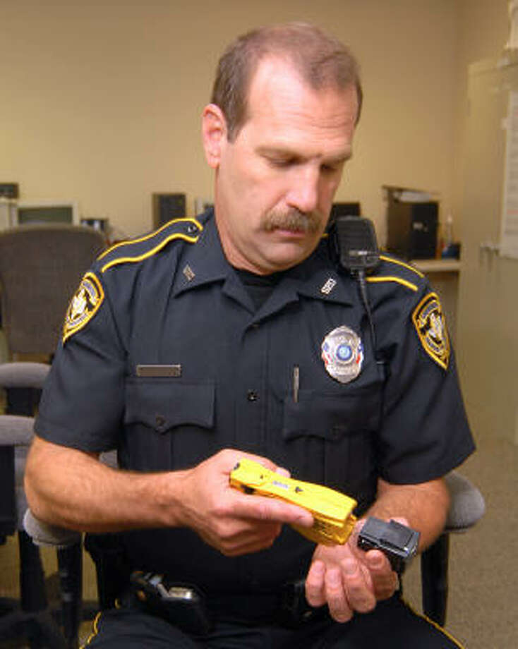 Shenandoah police officer Mark Denham examines the Taser he carries while on duty. The module holding the probes clips onto the yellow body of the Taser. He is the training officer for his department. Photo: David Hopper, For The Chronicle