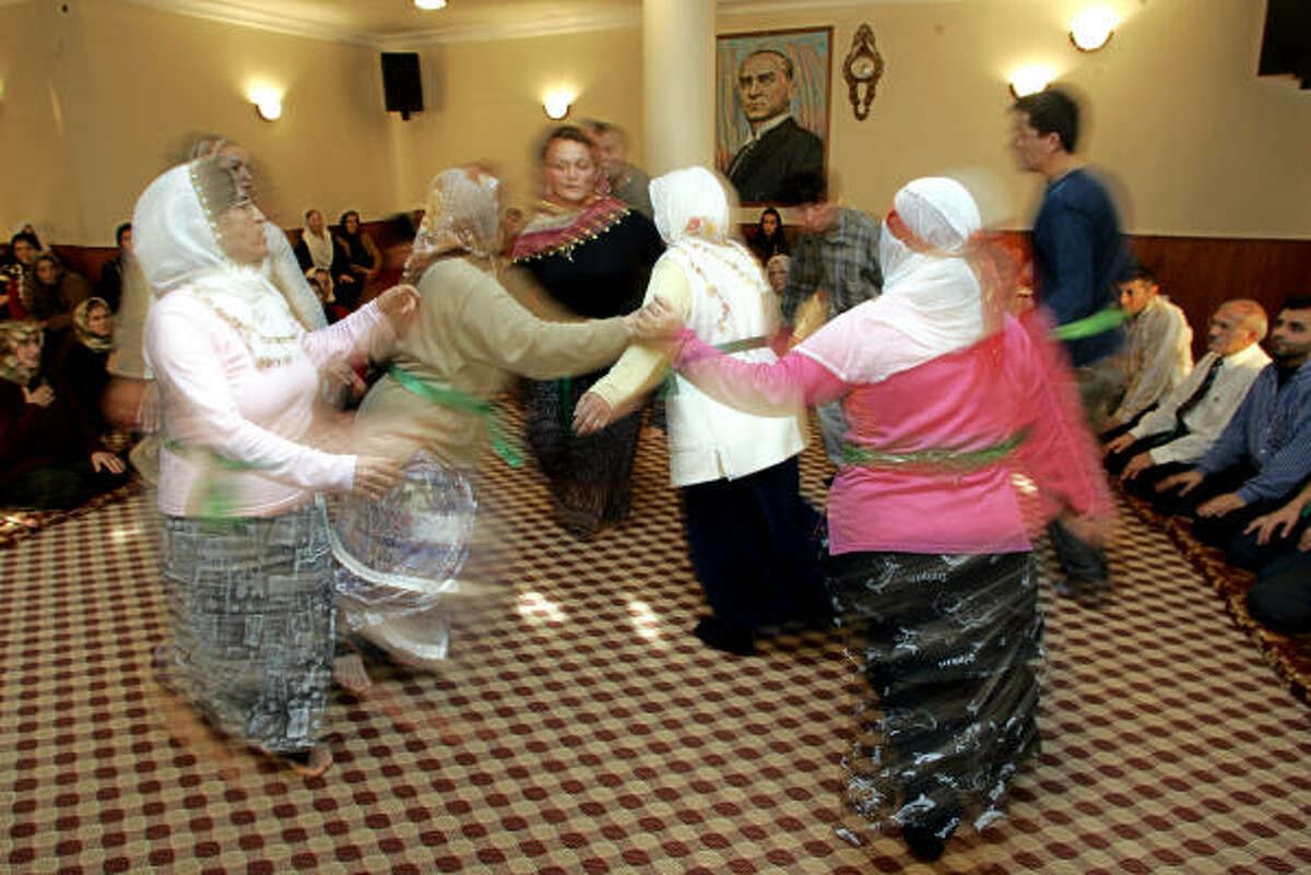 Alevi men and women perform a semah dance in a cem ceremony at the Karacaahmet cem house in Istanbul.