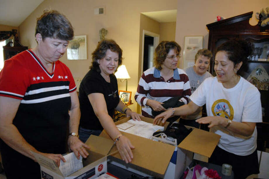 Anne Zesiger, left Aglaee Nicolas, Bonnie Black Mary Smith and Estela Campbell pack up supplies for soldiers in the hospital in Iraq. Photo: Kim Christensen