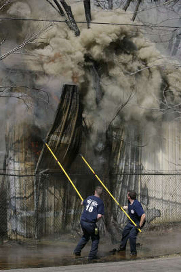 Houston firefighters strip a metal piece while trying to put out a three-alarm fire at the K&P Transportation Company warehouse in the 700 block of Delmar today. Photo: Julio Cortez, Chronicle
