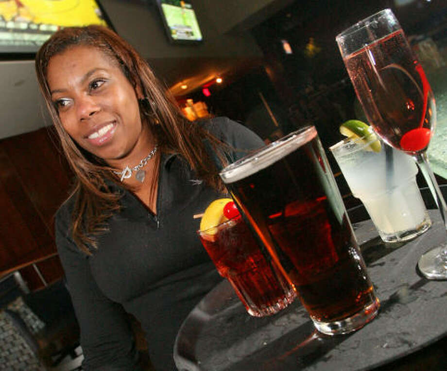 Thirsty customers at Fox Sports Grill await their reward from waitress Tina Thompson. Photo: Bill Olive, For The Chronicle