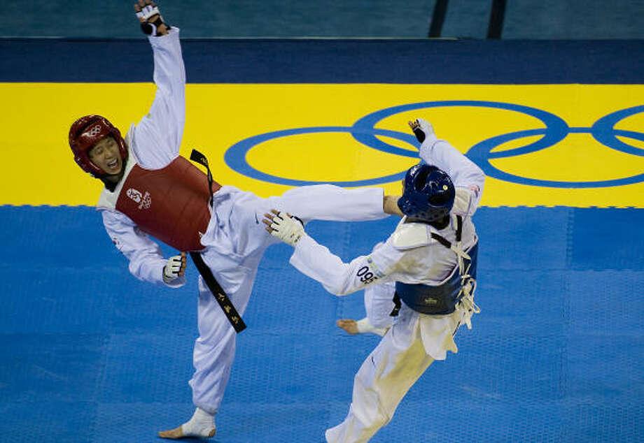 Son Tae-jin lands a kick on Mark Lopez. Photo: Smiley N. Pool, Chronicle Olympic Bureau