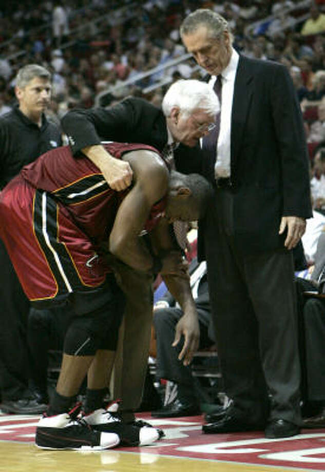 Heat guard Dwyane Wade is helped from the floor by trainer Ron Culp in the second half. Wade left the court in a wheelchair and was taken to a hospital. Photo: Pat Sullivan, AP
