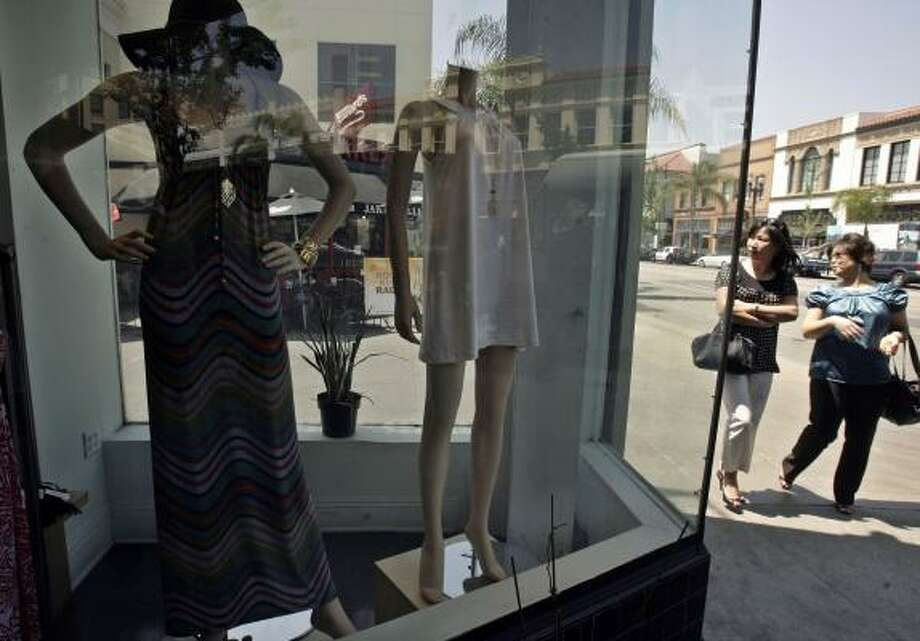 Pedestrians glance into the window of a boutique in Pasadena, Calif., on Tuesday. Soaring fuel prices and weaker job prospects made Americans gloomier about the economy in April. Photo: RIC FRANCIS, ASSOCIATED PRESS
