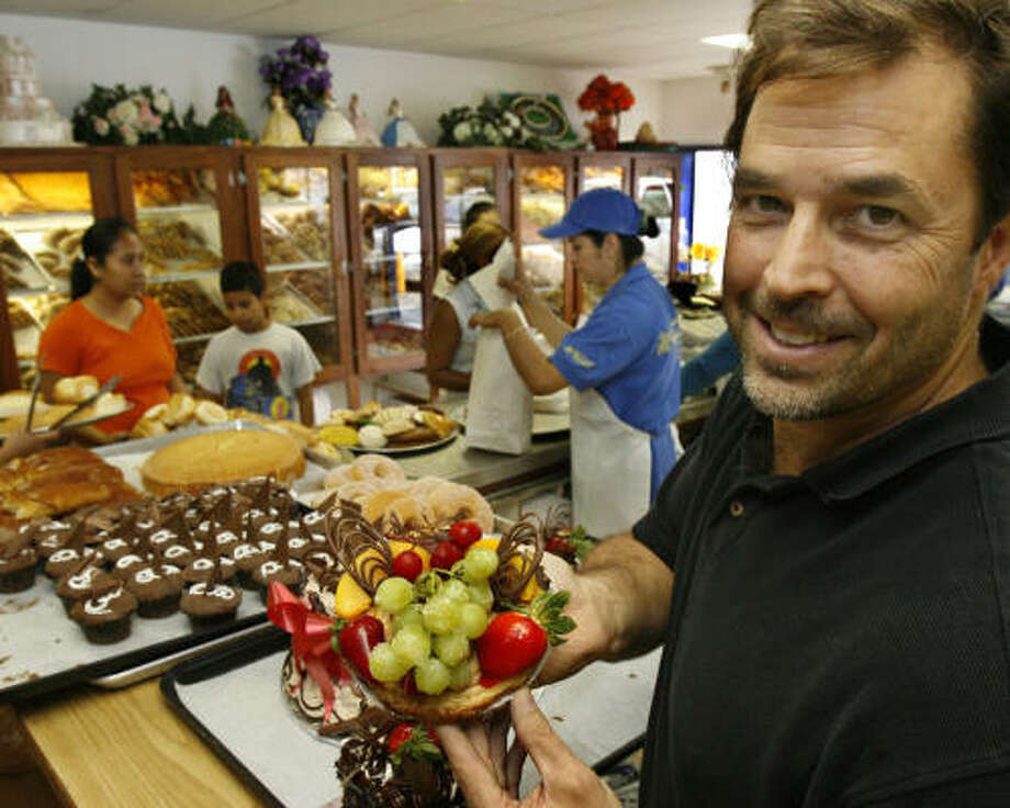 Kirk Michaelis, who co-owns El Bolillo Panaderia, shows off an ojarasca dessert, a crunchy cookie lightly covered in sugar and cinnamon, beneath chocolate and fruit. Photo: Carlos Antonio Rios, Chronicle