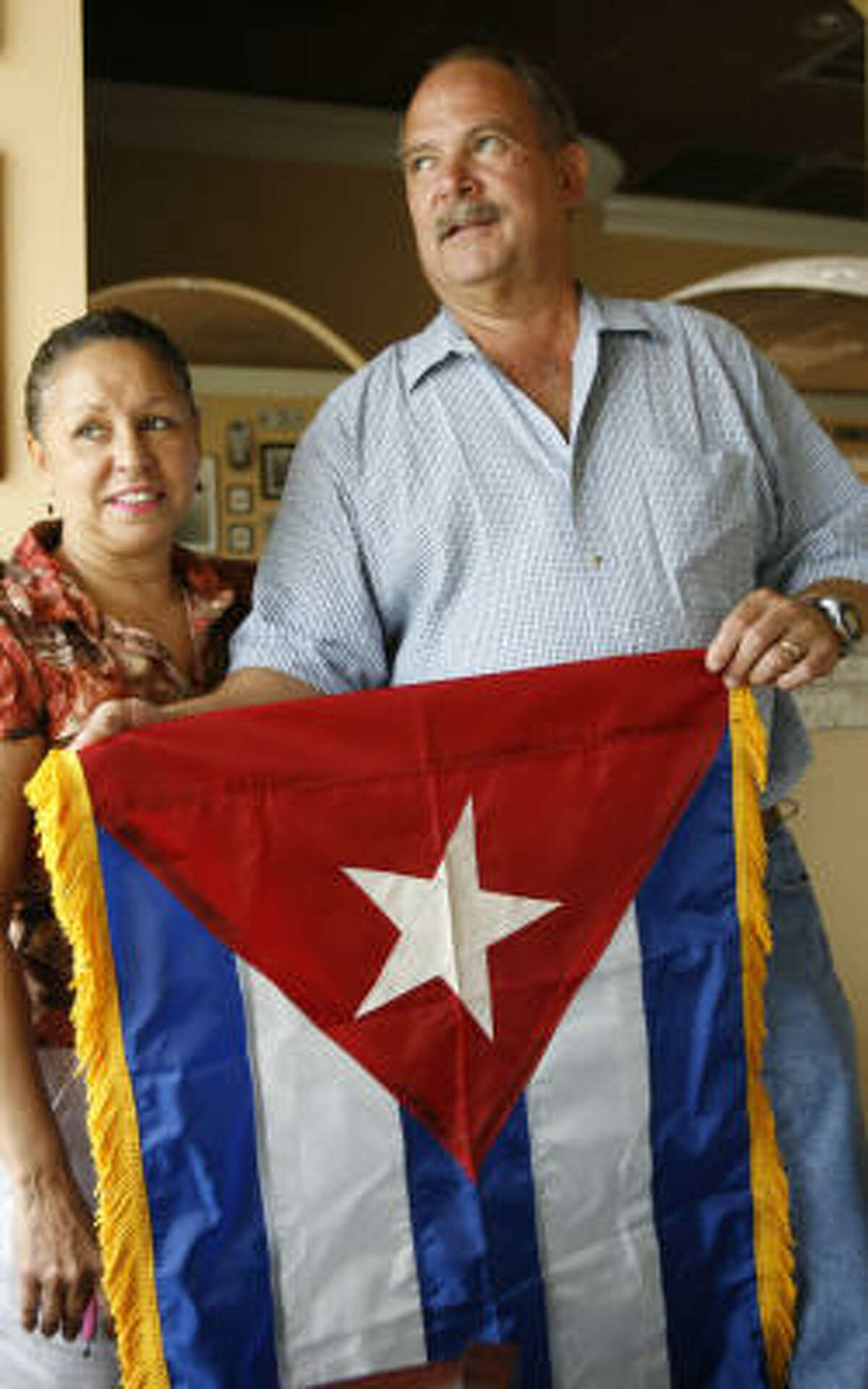 Guido Piquet, right, owner of Cafe Piquet on Bissonnet, and his wife, Nelly, hold a Cuban flag that was given to them several years ago.