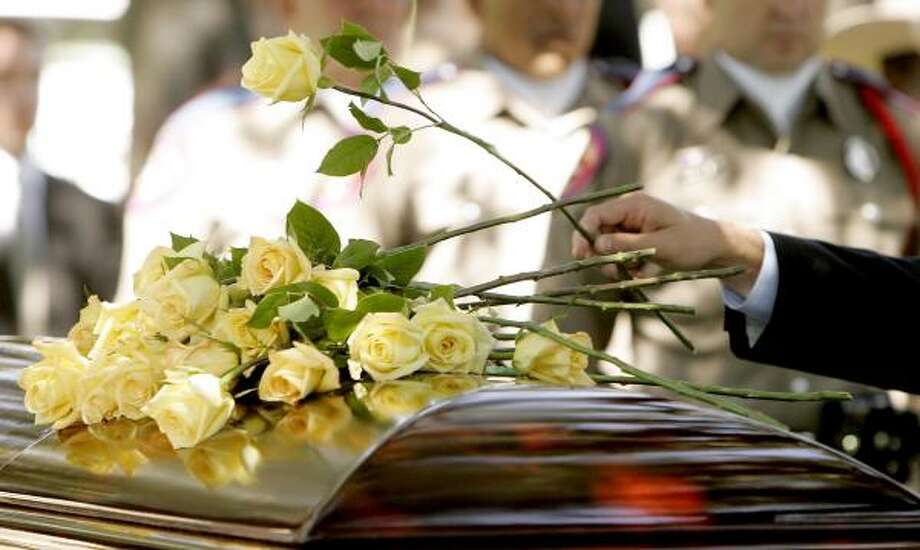 Family members place yellow roses on the casket of former Texas first lady Nellie Connally. Photo: ERICH SCHLEGEL, AP