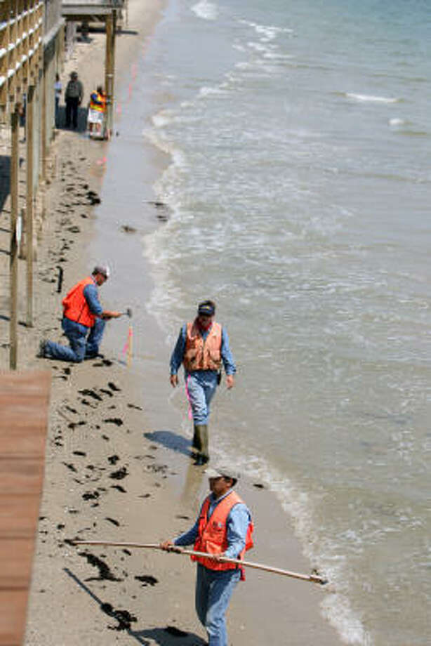 Texas General Land Office workers place stakes Thursday along the shoreline in Surfside. Photo: Sharon Steinmann, Chronicle