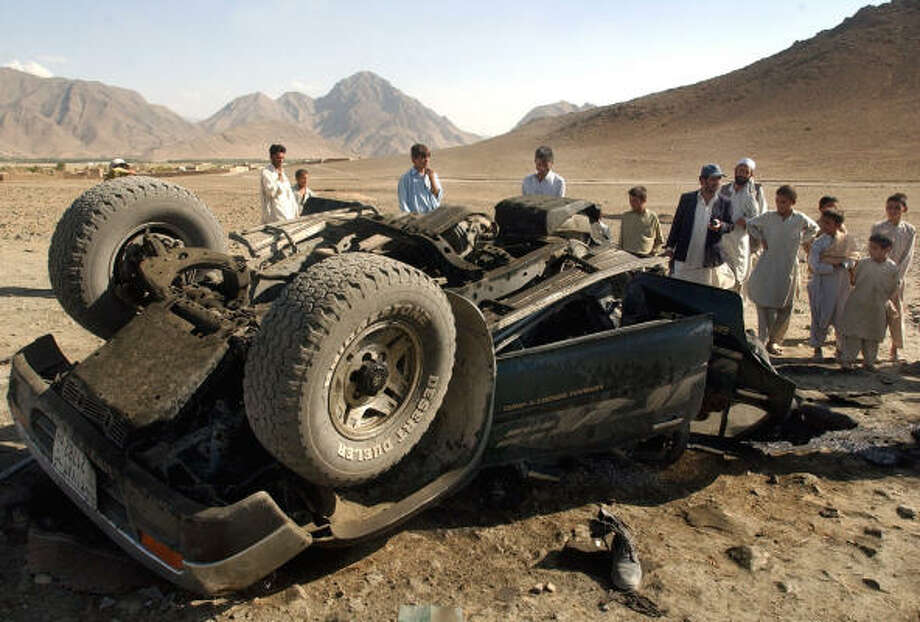 Villagers inspect a vehicle after it was blown off the road in a blast from a remote-controlled bomb Saturday on the outskirts of Kabul, Afghanistan. Photo: MUSADEQ SADEQ, AP