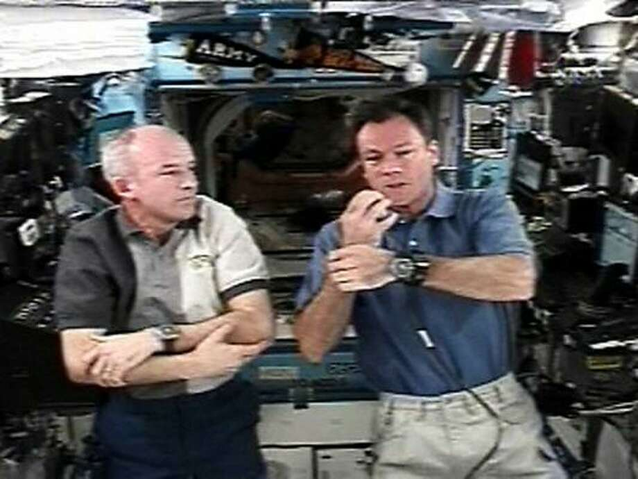 Expedition 13 crew member Jeff Williams, left, watches as Expedition 14 Commander Michael Lopez-Alegria shows an experiment he is wearing next to his wrist watch during a news conference from the International Space Station. Photo: NASA TV, REUTERS