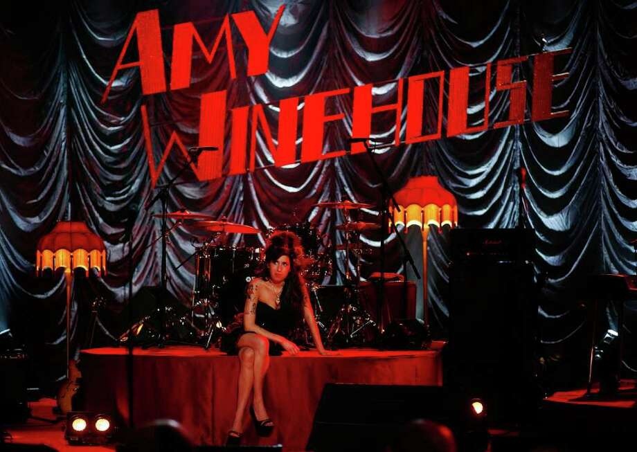 British singer Amy Winehouse sits on stage and looks up at a television monitor while awaiting news of her Grammy Award at The Riverside Studios for the 50th Grammy Awards ceremony on Feb. 10, 2008 in London, England. Photo: Peter Macdiarmid, Getty Images For NARAS / 2008 Getty Images