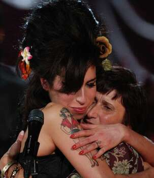 LONDON - FEBRUARY 10:  British singer Amy Winehouse (L) hugs her mother Janis after accepting a Grammy Award at The Riverside Studios during the 50th Grammy Awards ceremony via video link on February 10, 2008 in London, England. Photo: Peter Macdiarmid, Getty Images For NARAS / 2008 Getty Images