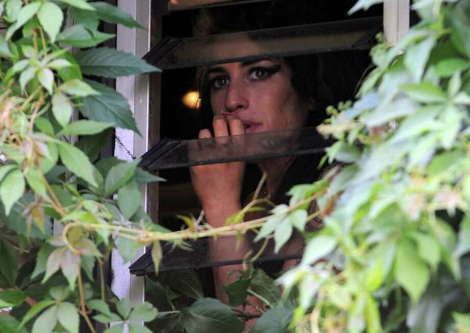 Singer Amy Winehouse eats sweets and chats to local kids out the window of her North London home on June 11, 2008 in London, England. Photo: Gareth Cattermole, Getty Images / 2008 Getty Images